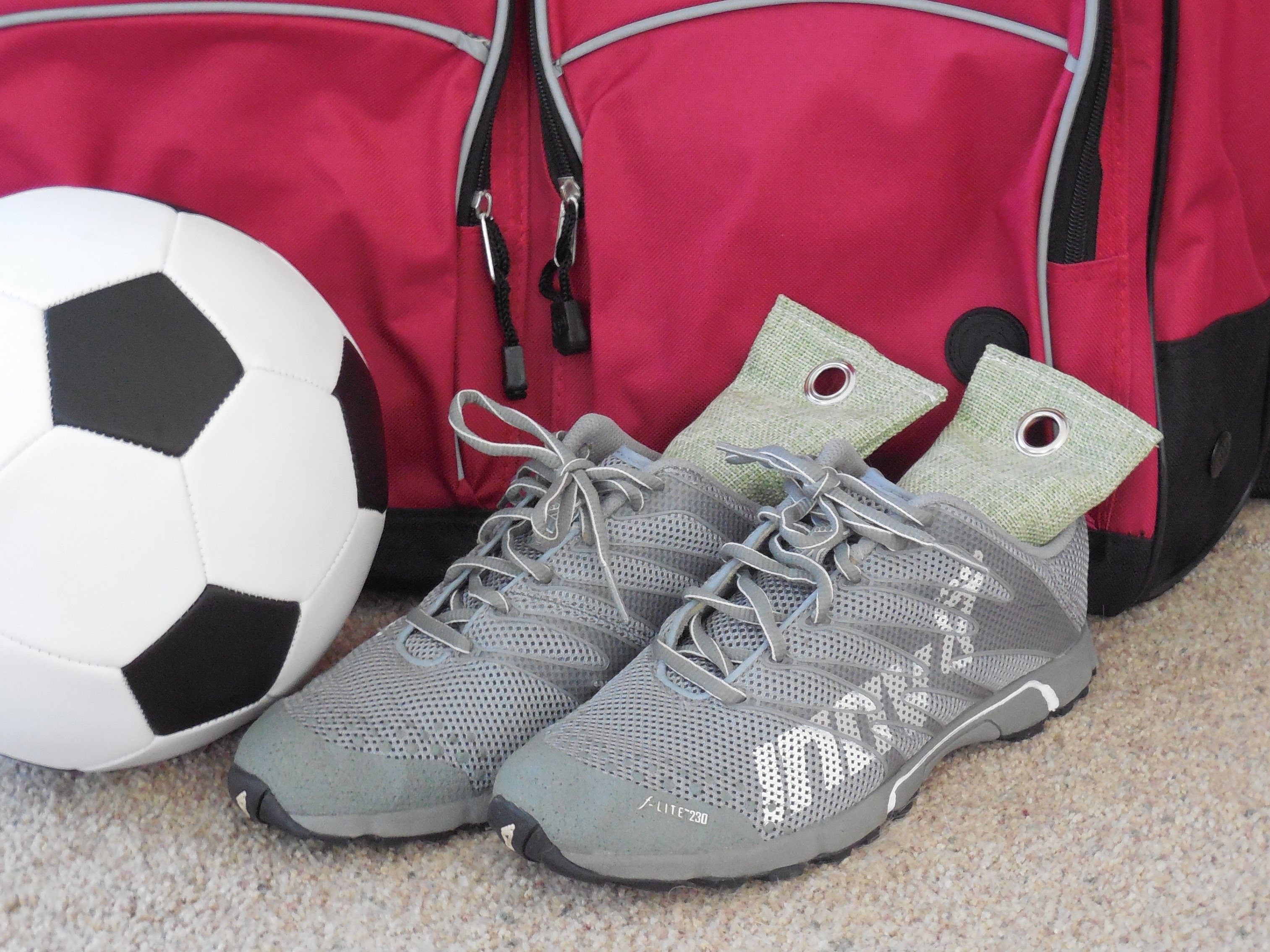 deodorizers inside sports shoes with soccer ball and red gym bag in background