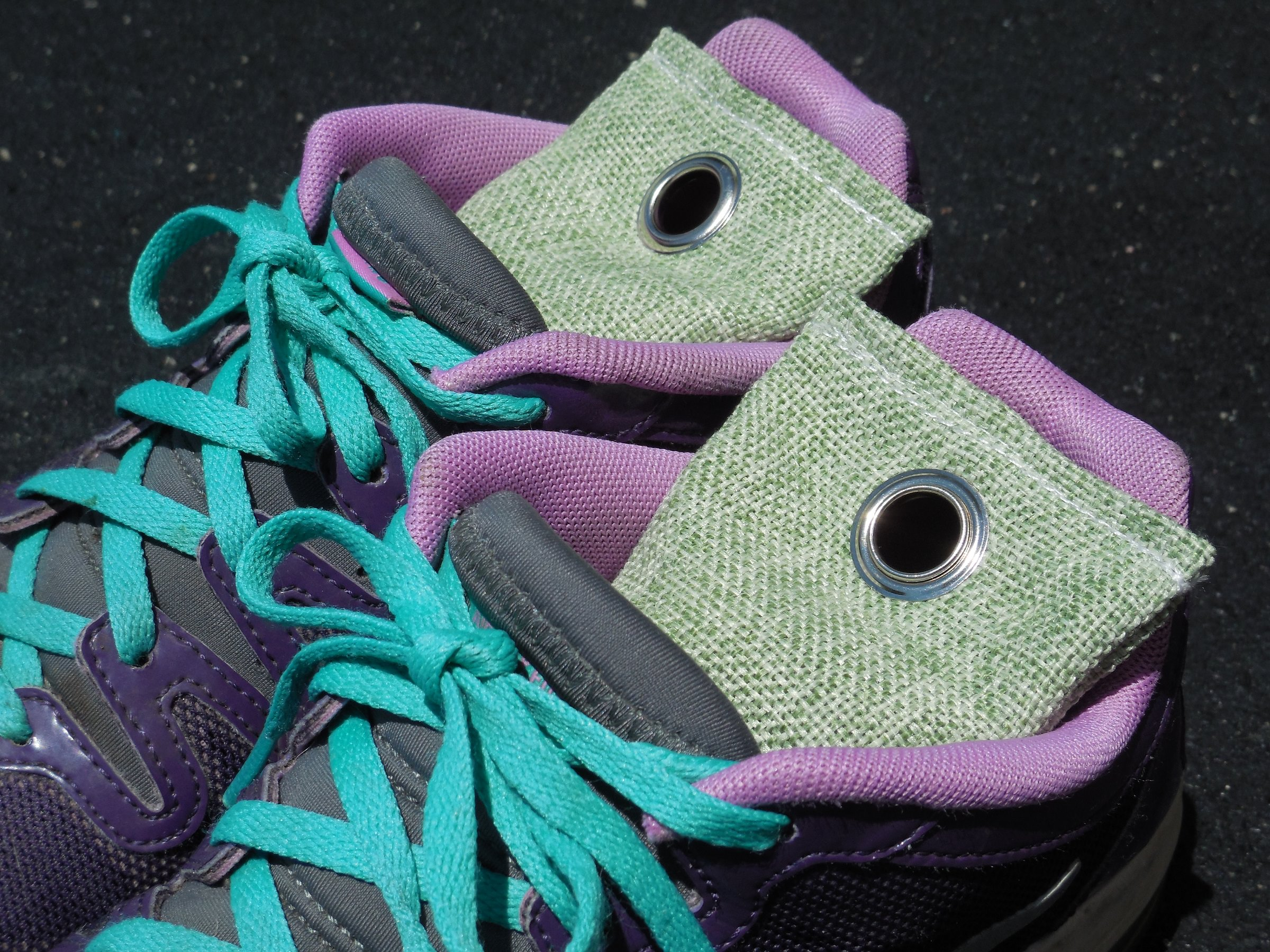 green fabric charchoal deodorizers in a pair of purple sneakers