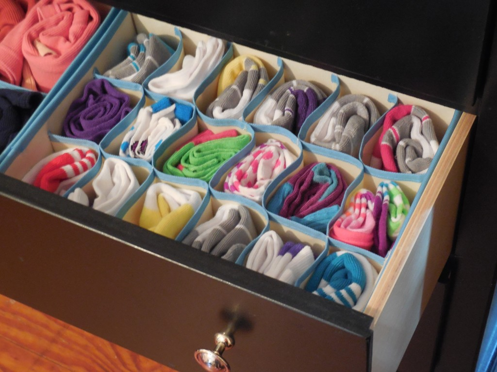 colorful socks displayed neatly arranged in the organizer sections inside a dresser drawer